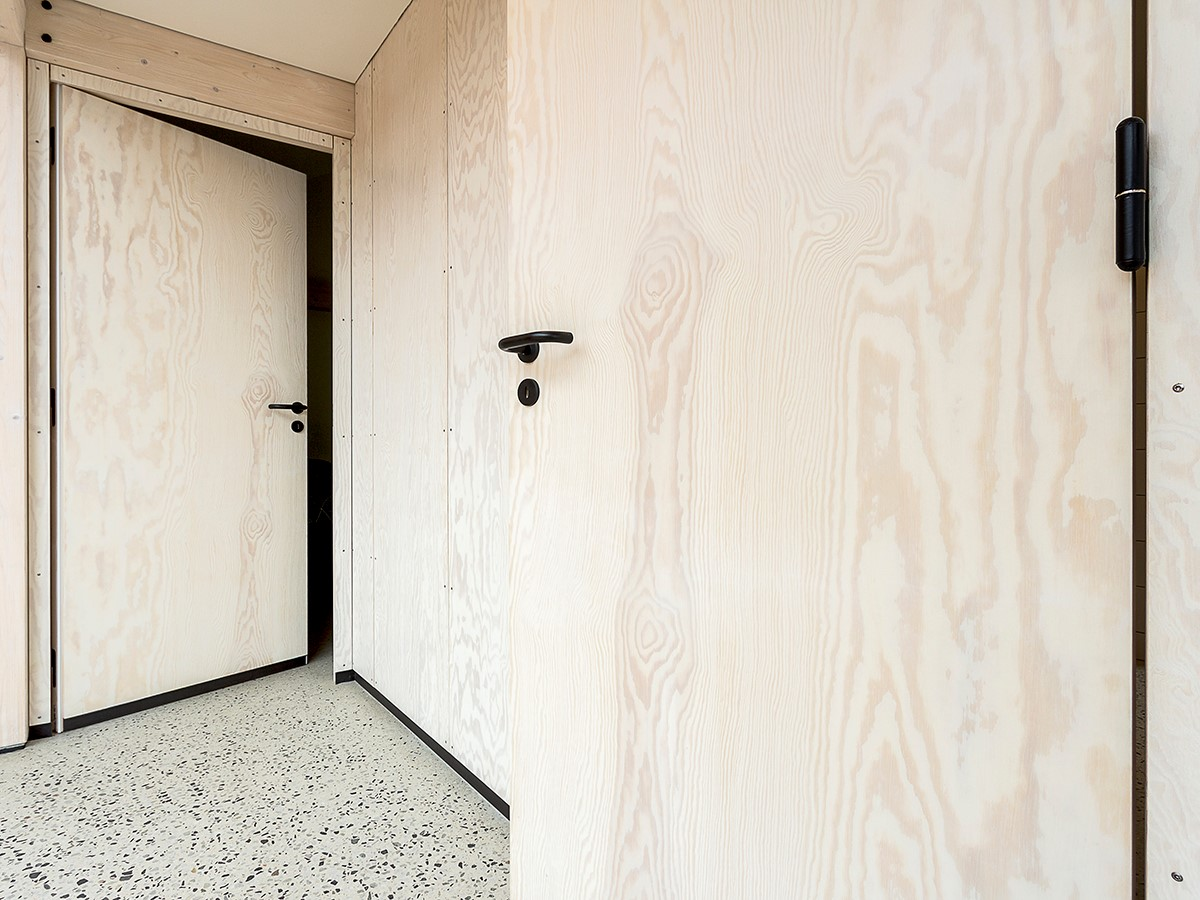 Moderne døre af krydsfinér har dørgreb og hængsler i sort. | Modern doors made from plywood with black door handles and hinges.