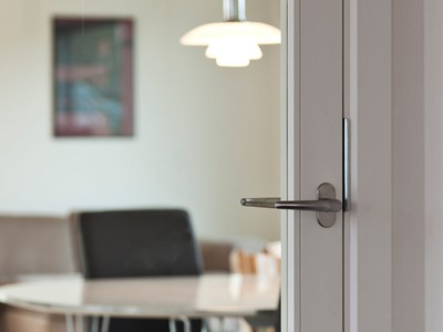 Glasdør med dørgreb af stål. | Glass door with door handle made from steel.